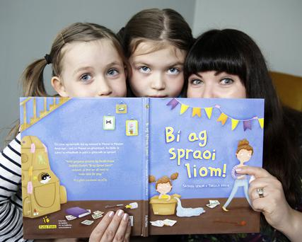Sadhbh Devlin with her daughters Sábha and Lile and her new book Bí Ag Spraoi Loim