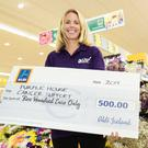 Stephanie Murphy from Purple House Cancer Support collects the cheque from Aldi