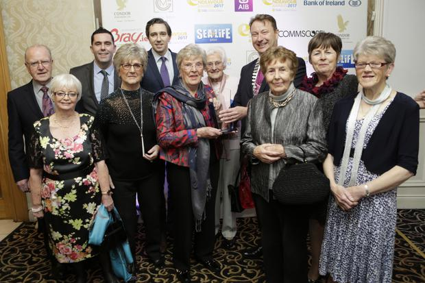 Kevin O'Loughlin from sponsor CommScope, Minister Simon Harris and Bray Chamber president Pat Ó Súilleabháin presenting the Community Award to Bray Old Folks Association.