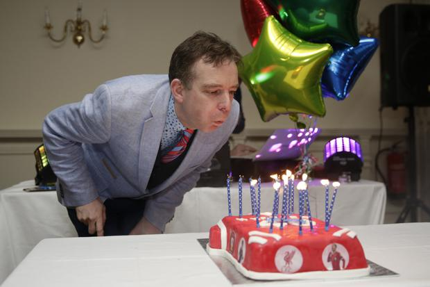 Martin blows out the candles on his cake.