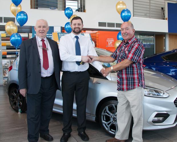 Dan Quill, chairman of Bray Credit Union, and John O'Brien from Fitzpatrick Motors present John Fleming with his car (Photo: Charlie Sharke).