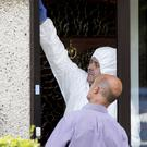 Forensic gardaí examine bullet holes in the doorway of the house at Rathsallagh Park in Shankill