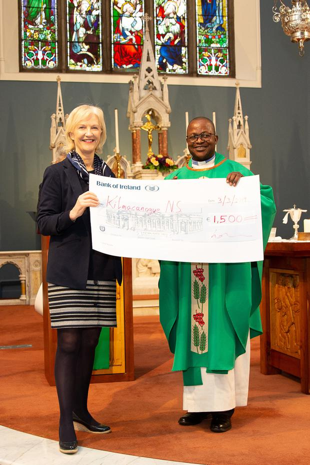 Soloist Niamh Murray, on behalf of Kilmacanogue NS, accepts a cheque for €1,500 from Fr Joseph Apust.
