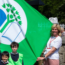 The Green Schools committee at St Mary's and St Gerard's NS, Enniskerry, raising the flag alongside Cllr Melanie Corrigan and Rory O'Connor