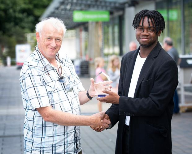 Art O'Laoghaire of Bray Area Rough Sleepers accepts the Bray Retail Park Local Heroes Award from Dafe Orugbo of 1Plus Events