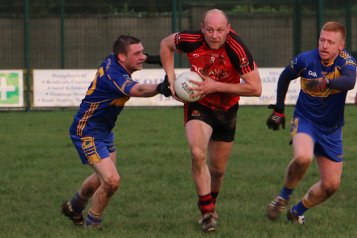 Coolkenno's Don Jackman slips through the cover of Carnew's Adrian Myers and Niall Osborne