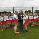 Kiltegan joint captains, Trish Kehoe and Elisha Ryan, collect the Junior Cup from Wicklow County Camogie Chairman Serge Goetelen.