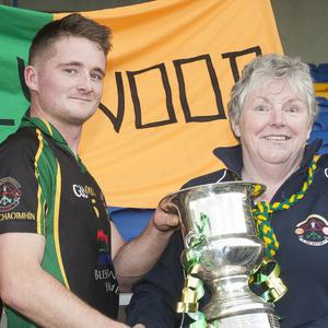 Hollywood captain Conor Burke receives the cup from Vice Chairman Martin Fitzgerald and Hollywood club secretary Lucy Mooney