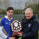Coláiste Bhríde Carnew captain Conor Hughes collects the South Leinster trophy from Pat Henderson