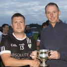 Newtown captain Dean Odlum collects the Division 2 cup from Wicklow County Chairman Martin Fitzgerald