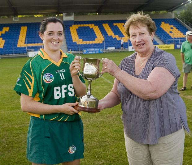 Knockananna captain Sinead Byrne is presented with the league cup by Chairperson of Wicklow Camogie Breda Byrne