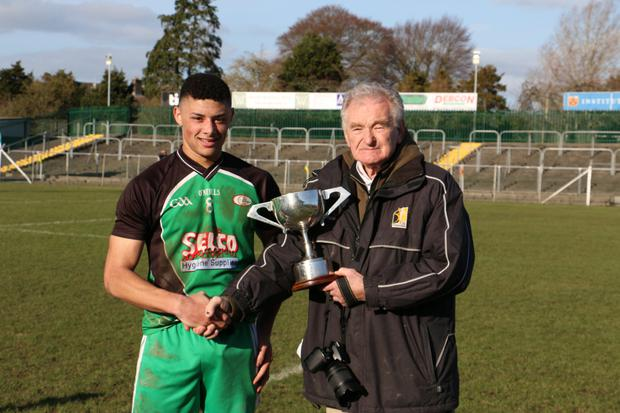 Kilkenny's Pat Henderson presents Scoil Chonglais captain Jordan Deans with the South Leinster 'D' cup.