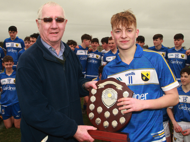 Jim Murphy presents Coláiste Bhríde's Owen Young with the South Leinster 'C' trophy after their win over Wexford CBS