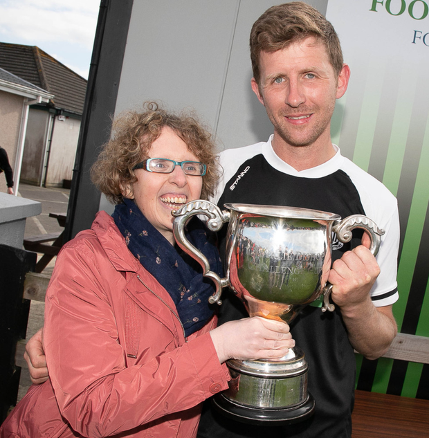 Newtown United's captain Neilly Martin accepts the Charlie Bishop Cup from Karen Bishop