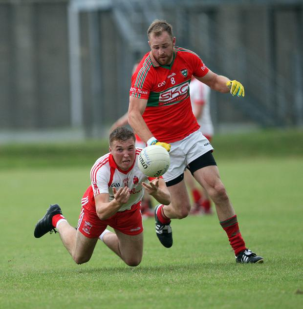 Tinahely's Rory Stokes gets his pass away as James Stafford closes in