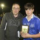 Brendan Lawrence presents Eire Og's Fionn O'Connor with the Wicklow People Man of the Match award