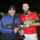 Mick Hagan presents the Schweppes Cup to Rathnew captain James Manley