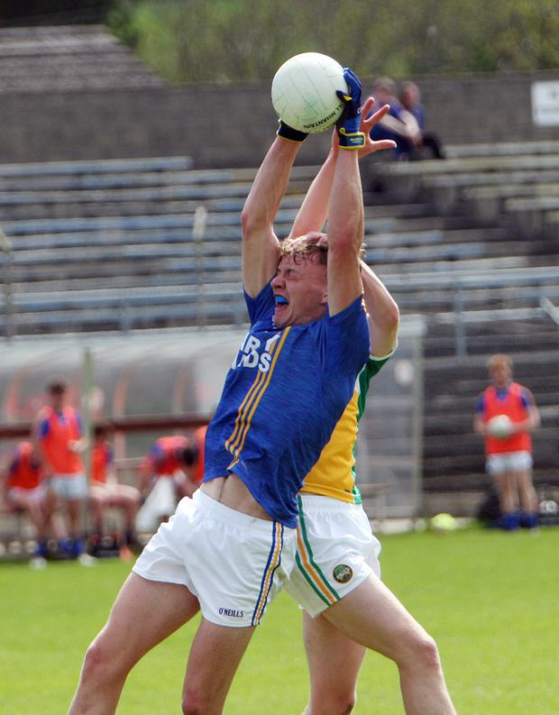 Wicklow's Eoghan Byrne gathers possession ahead of Offaly's Cathal Donoghue