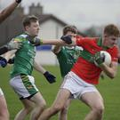 Cian Coffey of Rathnew battles past Jason Huntley and MJ Moran of St Nicholas during their Under-20 football championship match.