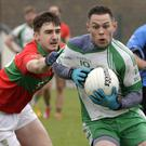 John McGrath of Baltinglass is tracked by Rathnew's Jamie Snell and Gary Byrne