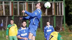 Robin Byrne of Roundwood gets his head to the ball