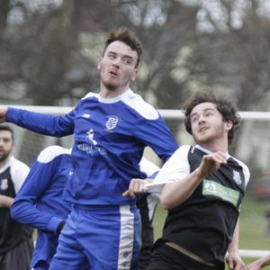Anto Byrne of Ashford Rovers gets his head to the ball ahead of Evan Moran of Newtown United.