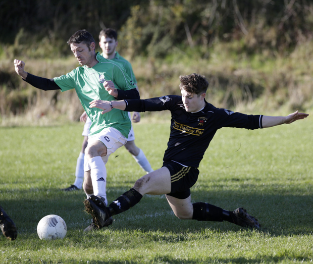PJ Dowling of Newtown United is challenged by Avonmore's Ryan Cahill