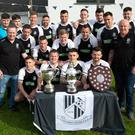 The Newtown United Senior squad and managers Gary Kelly and Dave Moran with the Charlie Bishop Cup, Andy McEvoy Premier Division trophy and the Tommy Heffernan Shield