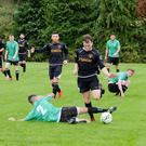 Callum Percy of Avonmore is tackled by Brandon Feehily of Newtown United