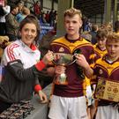 Ciara O'Sullivan, Cork senior footballer, presenting the Roinn F4 trophies to Whitechurch NS captain, Ryan Lynch and vice captain, Micheal Mullins following their win over Ballinora at the Allianz Sciath na Scol Finals at Pairc Ui Rinn