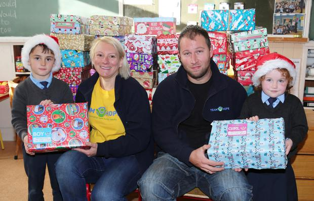 Daniel Quinn and Alanna O'Donoghue presenting their Christmas Shoe Box gifts to Sarah Janman and Ian Jordan from Team Hope. Photo by Sheila Fitzgerald