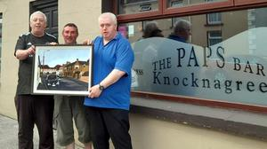 Local artist and teacher Laurence Hickey, centre, presenting his painting of O'Connell St, Knocknagree to Seán and Jerry Reen of The Paps Bar as a welcome-back present