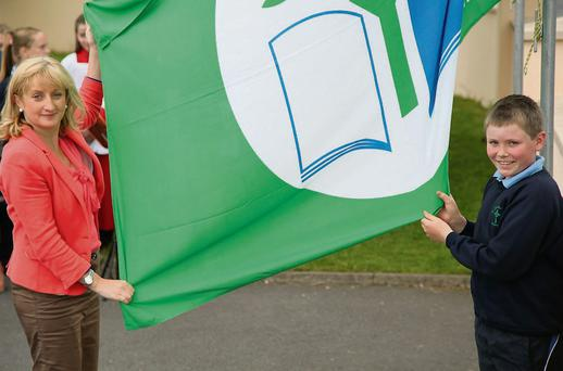 Past pupil, and parent, Aine Collins TD, helps pupil Neil O'Leary to raise the first Green Flag at St. Brendan's National School, Rathcoole.