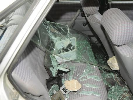 Broken glass and the rocks used to smash the windscreen and rear window of the car at the Men's Shed in Charleville.