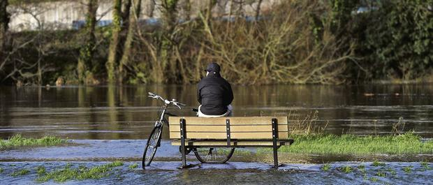 A cyclist takes a break along the flooded Lee Fields in Cork city on Monday.