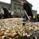 Swiss backers of a minimum universal income spread out coins at a recent rally in Bern. A whopping 76 per cent of voters were against the proposal