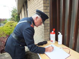 Superintendent Billy Dwane signs the book of condolence at Mallow Garda Station on Sunday.