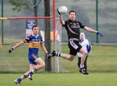 Kiskeam's Billy Dennehy shows athleticism to get a hand on a high ball early in his side's clash with Carrigaline in the County Premier Intermediate Football Championship last weekend. Photo: Eric Barry