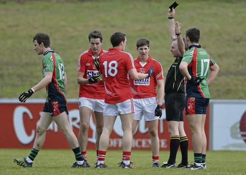 Michéal O Laoire, Cork, left, is shown a black card by referee Padraig O'Sullivan in the McGrath Cup in January