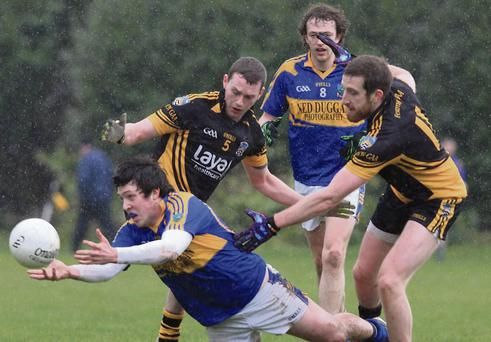 Ballyhooly's Kevin Kiely manages to get a handpass away despite being under heavy pressure from Fermoy's Kieran Dorgan and Ruari O'Hagan.