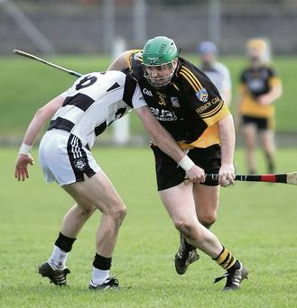 Fermoy's Paudie Shanahan powers his way past Ballyhea's Tim Shanahan