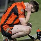 Duhallow hurler Barry O'Connor contemplates defeat after his team lost the County U-21 A Hurling Championship Final replay at Pairc Ui Rinn to Blackrock