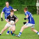 Lyre's Liam O'Brien attempts to evade a Kilbrin challenge in the Kanturk Credit Union Duhallow JAFC at Castlemmagner. Photo by John Tarrant