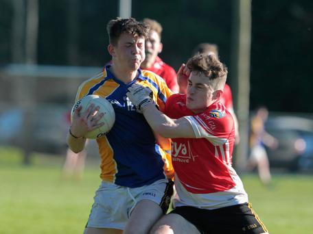 Seamus Madigan tries to protect the ball as he takes a hit from Fermoy's Paul Healy last Saturday during their North Cork U21B Football Championship game in Castletownroche Photo by Eric Barry