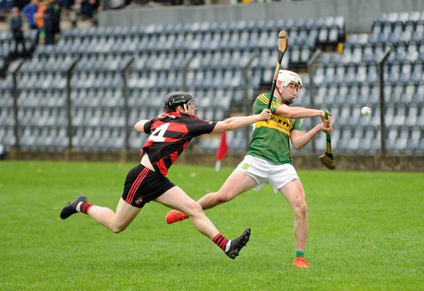 Mark Walsh, Cloughduv gets in his strike despite the strong challenge from Newmarket's Paudie Allen in the County Junior A Championship semi-final at Páirc Uí Rinn. Photo by George Hatchell