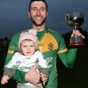 Boherbue captain Conor O'Riordan joined by daughter Lily after receiving the Duhallow Nevin Cup Junior B Football League title