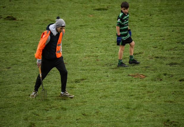 A young player from Douglas GAA watches as a groundsman attempts to repair divots on the pitch at half time during the Allianz Football League Division 2 Round 2 match between Cork and Kildare at Páirc Uí Chaoimh in Cork. Photo by Eóin Noonan/Sportsfile
