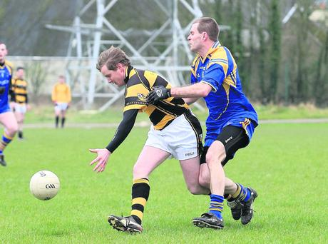 Buttevant's Denis O'Connell tries to get a hand to the ball whilst under pressure from Lisgoold's Jamie Hurley during the Division 1 league clash between the sides. Photo: Eric Barry