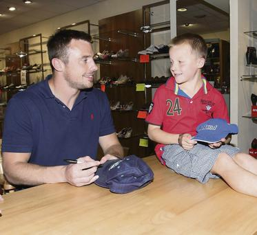 John Maher from Buttevant has a chat with rugby star Tommy Bowe, who was in Mallow promoting his new range of shoes.