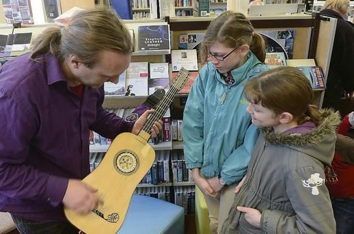 Eamonn Sweeney demonstrates guitars at the Meet the Instruments event in Ardee Library during last year's festival.